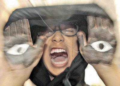 頭戴黑帽的年輕人「可樂」,特意把雙手塗成黑色,再於掌心畫上眼睛,代表整個香港已被黑影怪物籠罩。。(圖:東方日報提供)