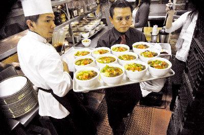 侯圳生(左)烹製牛肉麵,L' Olivier餐館侍應忙於上菜。(記者關文傑/攝影)