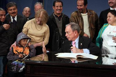 市長彭博18日簽署通過兩項減少犯輕罪移民被遞解可能性的提案,簽署儀式上和與會的移民小朋友親切互動。(市府提供)