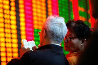 由於缺少中國證券公司的股票交易資料,美國國稅局只能依靠估計課稅。圖為兩名中國投資者在觀看股市行情。(美聯社)