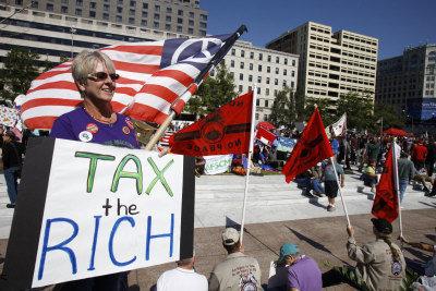 投資移民被要求向政府納稅。圖為一美國人打出的標語是:「向富人徵稅」。(美聯社)