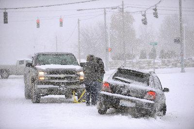 冰風暴6日襲捲美國中南部,造成數十萬人家中斷電,多州災情頻傳。圖為肯塔基州巴度卡一輛汽車(右)6日因大雪打滑困在溝渠中。(美聯社)