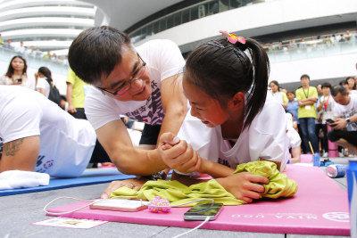 平板支撐世界杯賽22日在北京銀河soho舉行,2000多位平板支撐愛好者一齊衝擊「同時做平板支撐人數最多」的金氏世界紀錄。soho中國董事長潘石屹、「瑜伽女神」母其彌雅以及前美國駐華大使駱家輝偕出席活動。圖為駱家輝在完賽後為一名還在堅持比賽的11歲小選手加油助威。(中新社)
