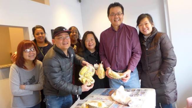 榴蓮派對: 馬來西亞會的鄭金光(右二),日前訂購了99磅的新鮮榴蓮,與所有新馬同鄉分享,鄉親品嘗久違的家鄉味,紛紛向鄭金光道謝。(圖:新馬同鄉會提供)
