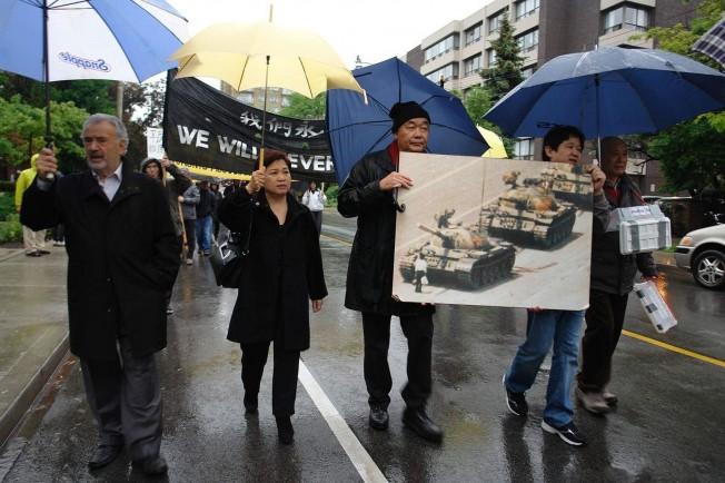 多伦多支持中国民运会主席关卓中(左三)、前联邦参议员狄尼诺(左一)、港加联发言人冯玉兰(左二)、民主中国阵线成员罗乐(左四)等数十人,先在中国驻多伦多总领馆前抗议后展开游行。(记者葛健生/摄影)