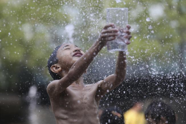 北京飆高溫,圖為孩子們在北京三里屯噴泉中戲水納涼。(中新社)