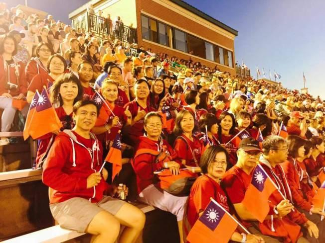 建中樂旗隊的隨行家長們,手持中華民國國旗在比賽現場為孩子們加油打氣。(建中樂旗隊提供)