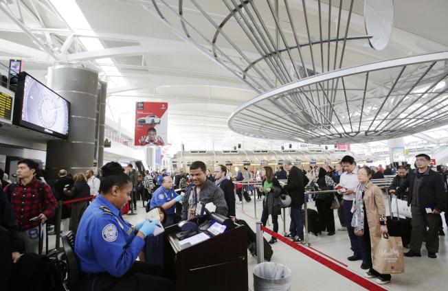 乘客在紐約甘迺迪機場出關時接受安檢。( 美聯社)