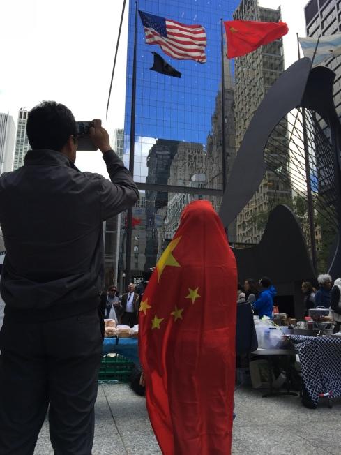 一位民眾披著五星紅旗到戴利廣場參加升旗典禮,與天空飄揚的紅旗巧妙對映。(記者黃惠玲/攝影)