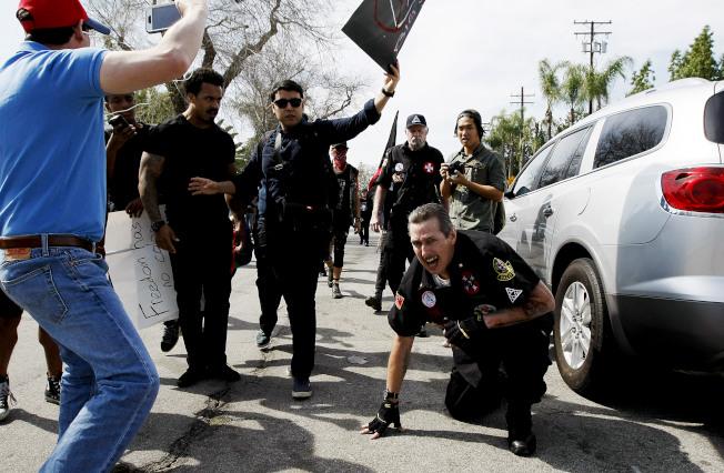 名三K黨員被打到蹲在地上,十分狼狽。(美聯社)