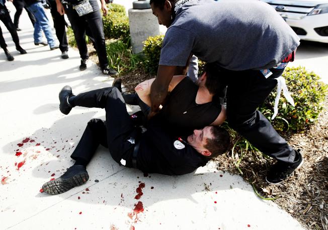 一名三K黨員與一名反制人士扭打,旁邊地上血跡斑斑。(美聯社)