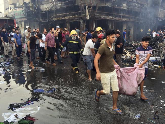 伊拉克消防人员和民众3日在遭汽车炸弹攻击的巴格达闹区将罹难者抬离。(美联社)
