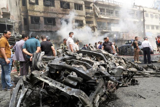 伊拉克首都巴格达2日晚发生汽车自杀炸弹客攻击,造成至少143人丧生,近200人受伤。图为民众3日聚集在发生爆炸的汽车旁。(路透)