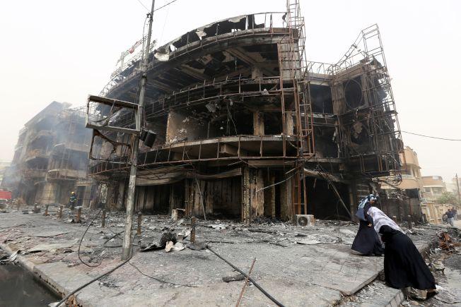 伊拉克首都巴格达2日晚遭炸弹攻击,造成至少143人丧生,近200人受伤。图为巴格达妇女在被炸得满目疮痍的建筑旁。(Getty Images)