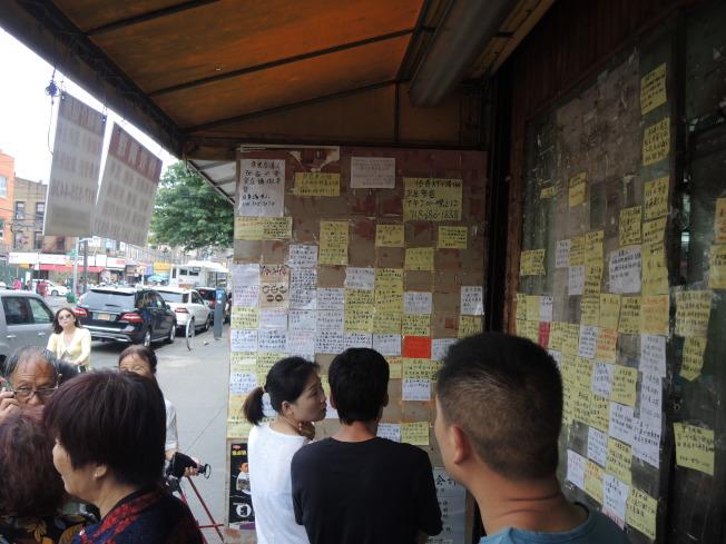 民众在8大道单位出租广告栏前查找心仪的单位。(记者王靖雯/摄影)