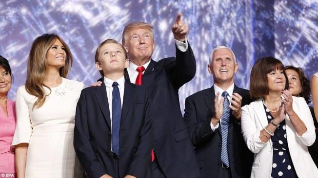 川普替他的小兒子拜倫指出,大會的慶祝汽球即將落下。左為川普夫人美蘭妮,右二為共和黨副總統候選人潘斯,右為潘斯夫人凱倫。(Getty Images)