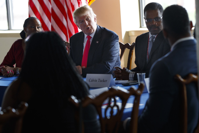 民調顯示,過去一周已有更多非裔選民轉向支持川普。圖為川普(中)2日在費城與非裔領袖會面。(美聯社)