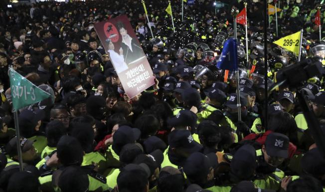 南韓總統朴槿惠因容許閨蜜崔順實干涉國政,引起民眾上街頭示威,要她下台。 (美聯社)
