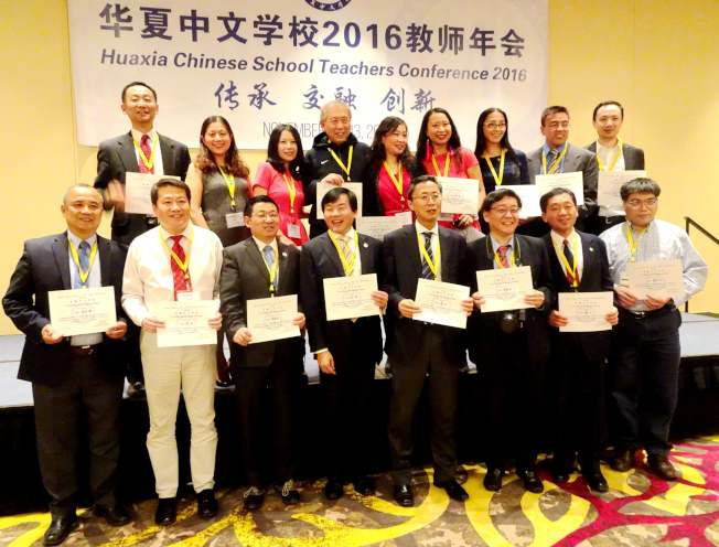 華夏總校校長張長春(前左一)為校內的志願者頒發獎狀,以表彰他們為學校和年會作出貢獻。(記者謝哲澍/攝影)