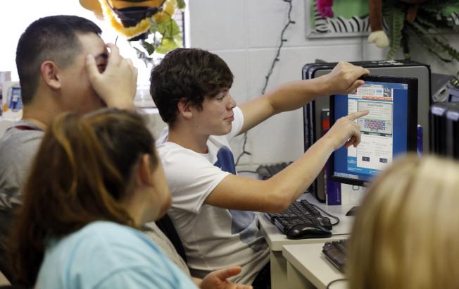密西西比州一所高中的學生,在電腦螢幕前展開討論。(美聯社)