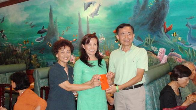 大奧蘭多台灣商會保齡球聯誼賽季軍張勁松(中)獲頒獎金,左為會長莊杏珠,右為僑務委員王成章。(Cynthia Jarboa提供)