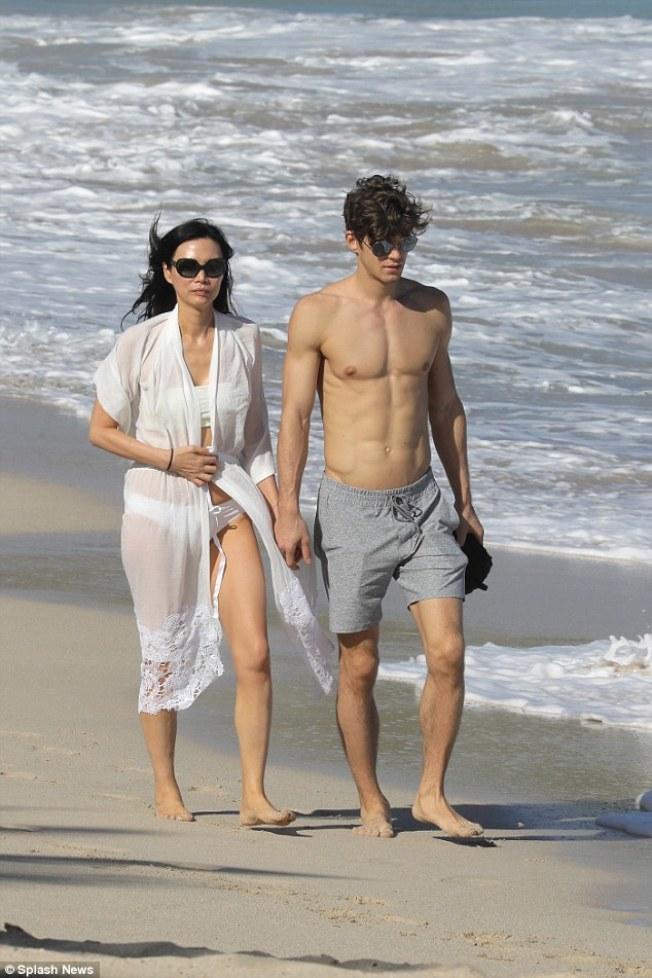 梅鐸前妻鄧文迪和小鮮肉在沙灘散步。(取材自英國每日郵報)