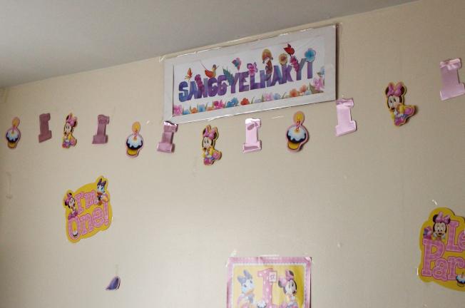 兇案現場牆上掛著女嬰的名字桑結‧拉吉,並貼有滿周歲的壁飾。(記者朱澤人/攝影)
