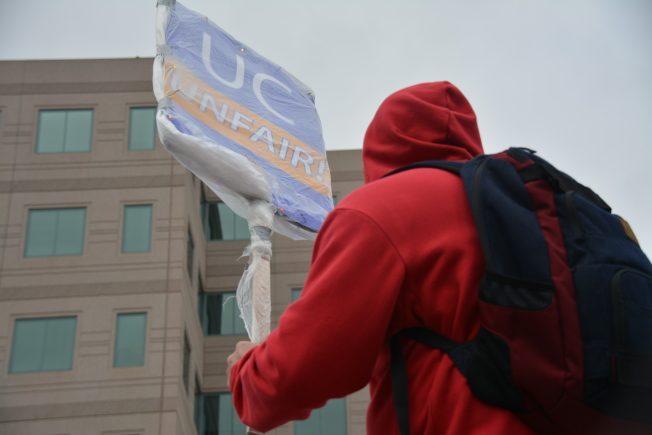10日洛加大行政文員發起聯合罷工,超過700人風雨無阻上街頭,高舉綁上透明塑膠袋防潮的標語爭取權益。(記者吳佩甄/攝影)