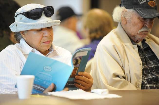 最新分析报告指出,美国退休者的预期寿命低于其他已开发国家,图为一名退休女子仔细研读防诈骗宣传手册。(Getty Image)