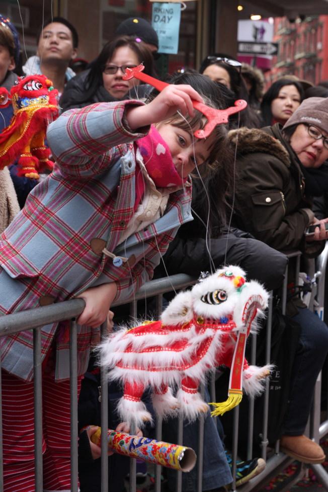 外族裔女童擺弄著舞獅玩具。(記者許雅鈞/攝影)