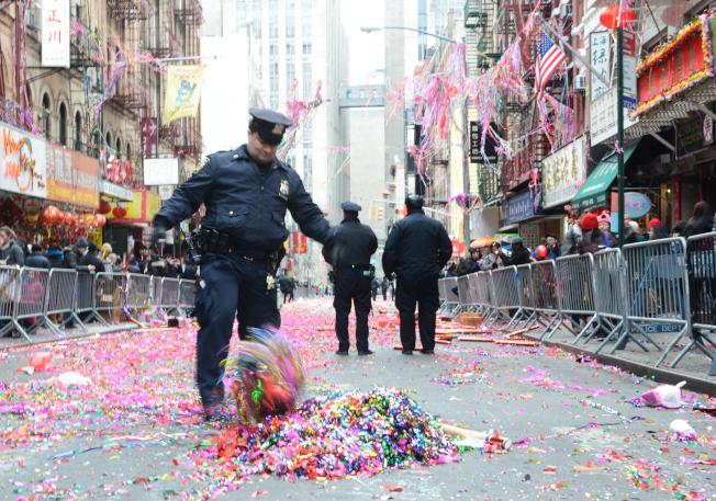 遊行後,街上盡是彩炮屑,一位警員將團團彩帶集中,以便清潔局人員清理。(記者許振輝/攝影)