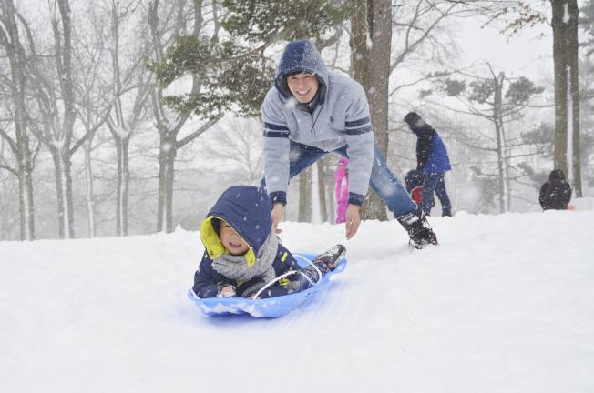 雪後的公園成了天然滑雪場,家長和孩子們玩得不亦樂乎。(記者俞姝含/攝影)