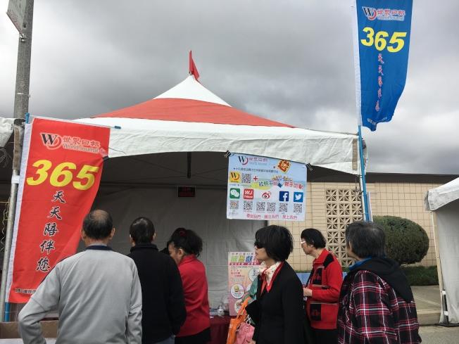 世界日報在四海迎春園遊會中設攤,民眾爭搶買報,當日隨報附贈的健康手冊也相當受歡迎。(記者莊婷/攝影)