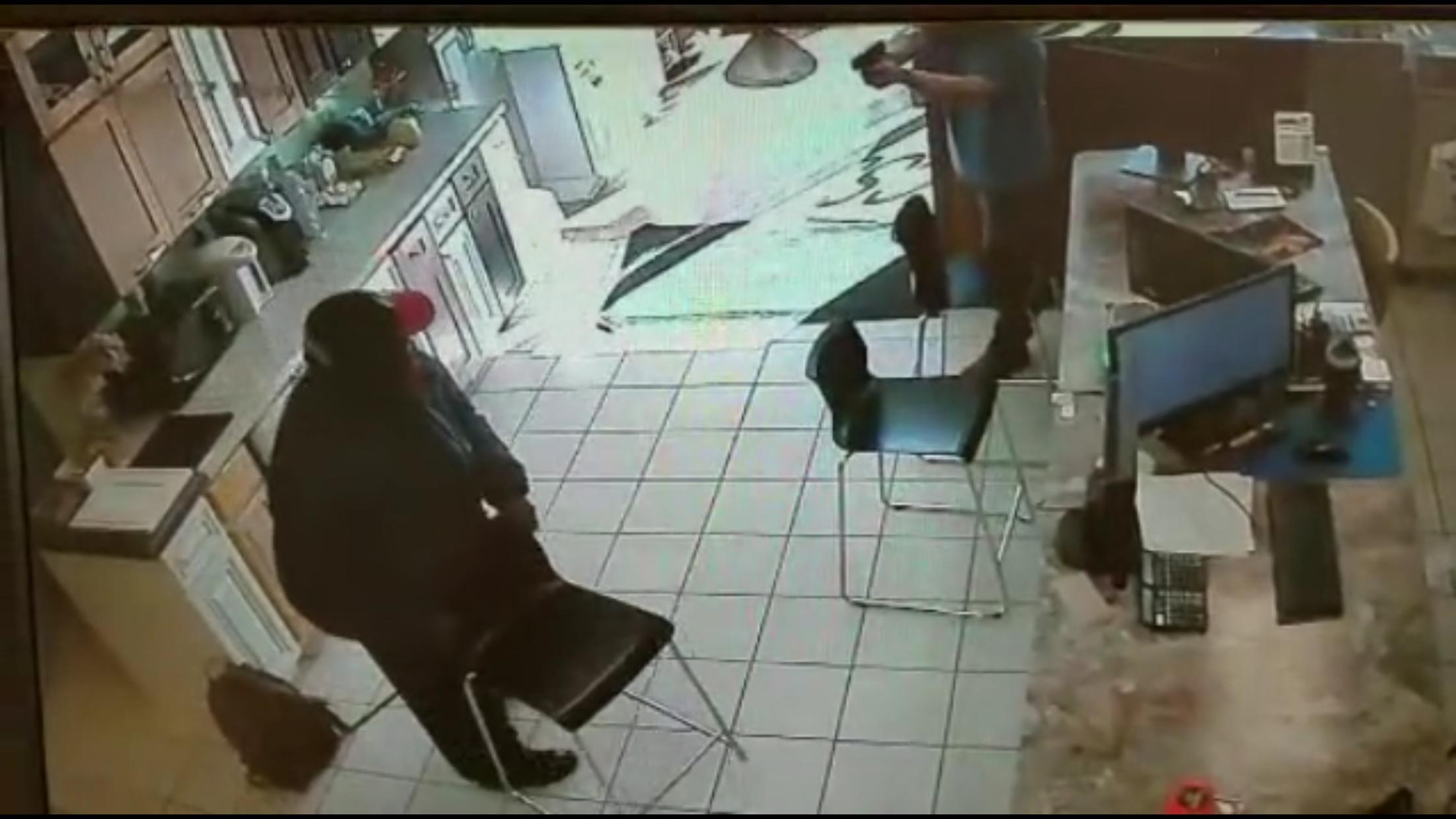非裔嫌犯進入金麟櫥櫃鬧事索財,被華裔店主譚一文拔槍嚇退。(監視影片截圖)