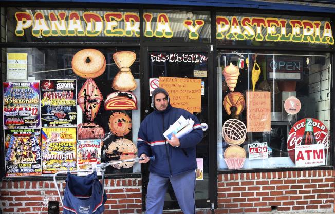 「無移民日」凸顯移民對美國商業的重要性。圖為費城一名郵差茫然地行經一間關閉的商店。(美聯社)