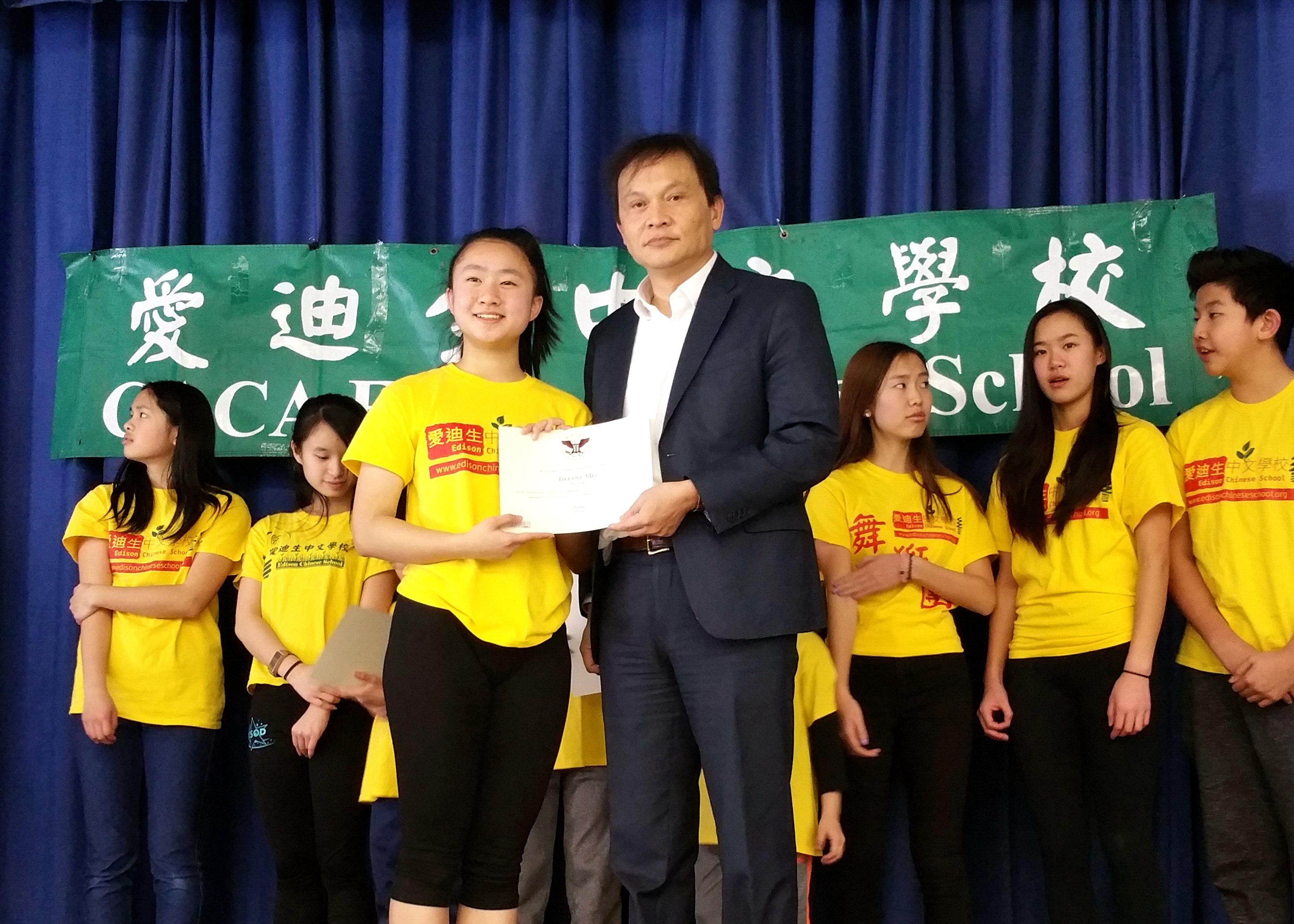 新澤西中文學校協會董事長戴松昌(前右),為榮獲總統志工服務獎的愛市中校華生頒獎。(新澤西中文學校協會提供)