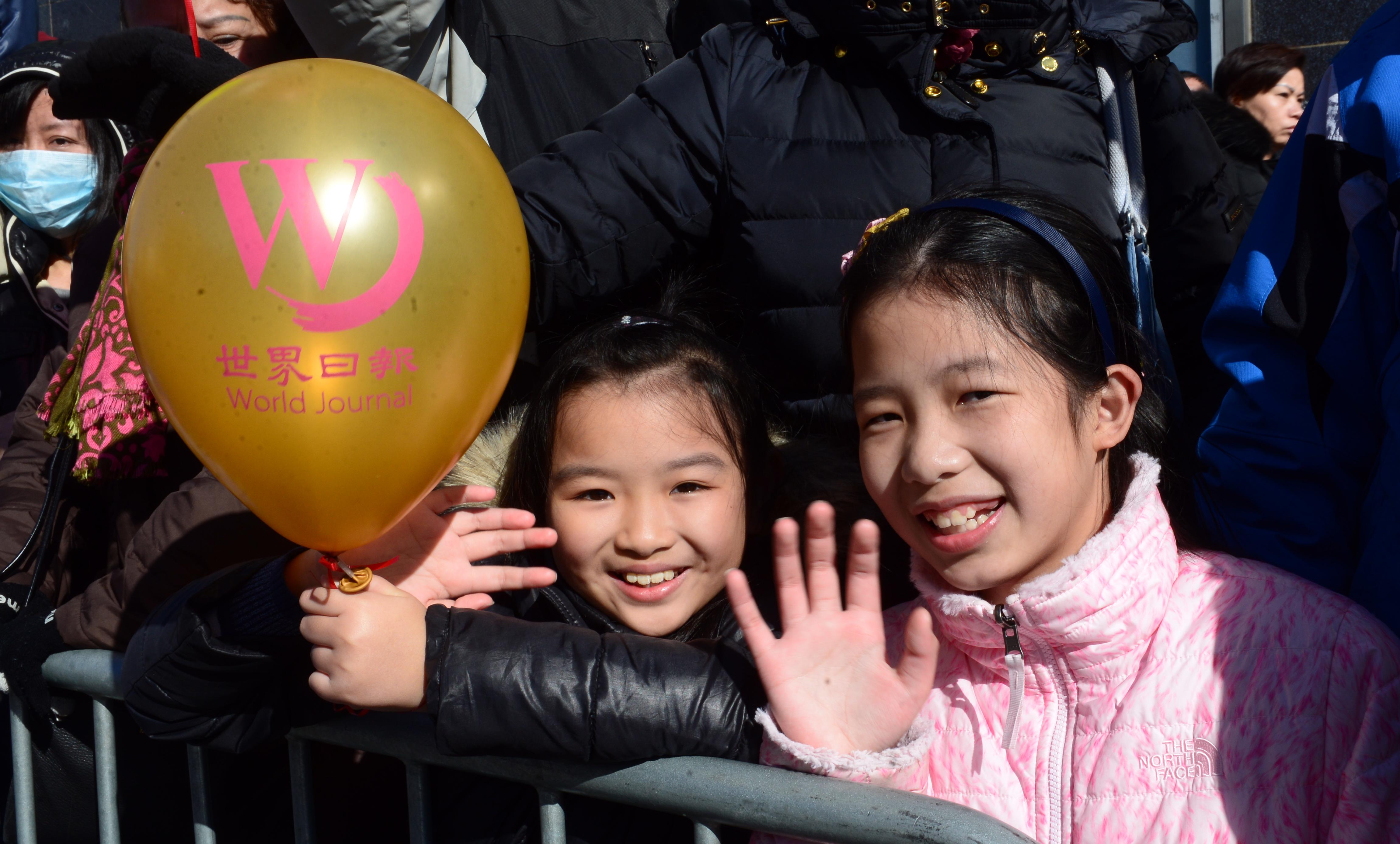 小朋友手持世界日報氣球觀賞遊行
