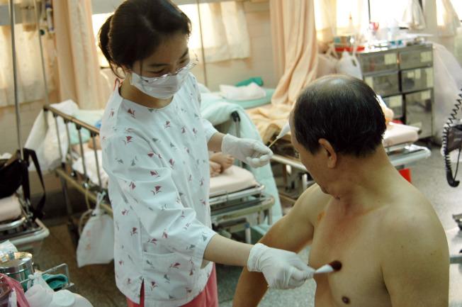 女護士為男病人擦藥。(本報資料照片)
