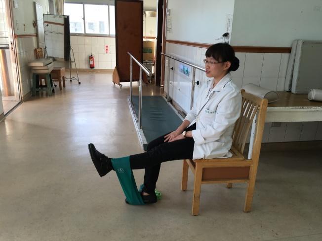 物理治療師邱新時教民眾簡單的運動,訓練腿部肌力,用腳將彈力帶拉起,有助於訓練腿部肌力。(記者陳麗婷/攝影)