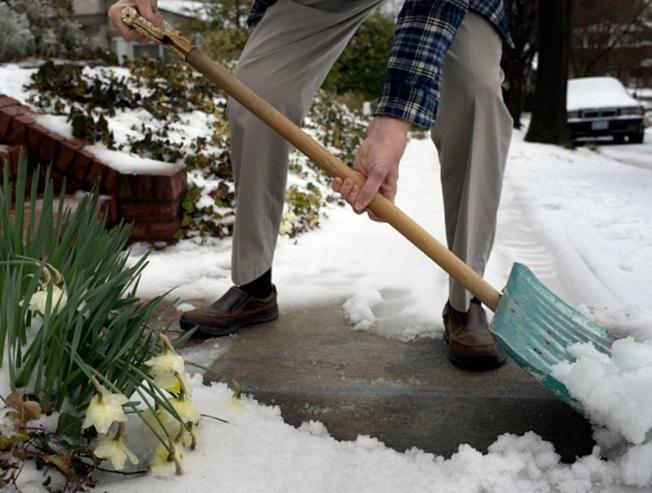 鏟雪時應兩腿分開下蹲,彎曲膝蓋,保持胸背挺直。(Getty Images)