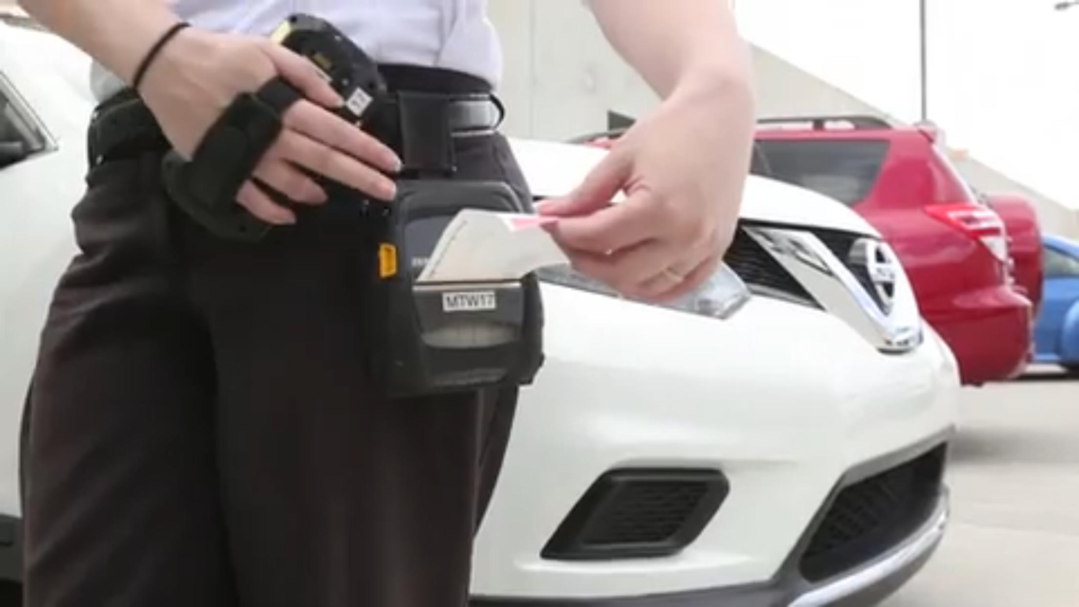 中佛大停車及交通服務部的員工,開罰單取締違規停車。(截自視頻)