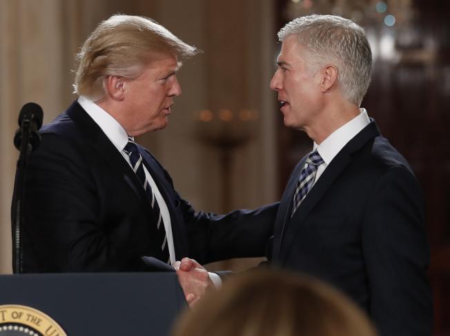 大法官提名人戈薩奇支持川普改變司法系統,圖為川普宣布提名後,與戈薩奇握手的資料照片。(美聯社)