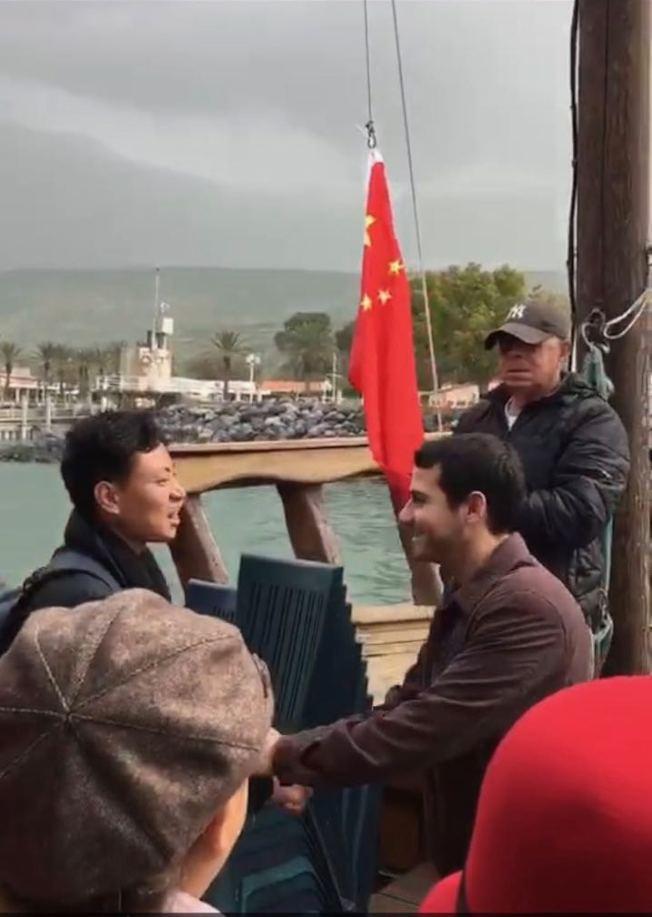 陸客受歡迎,業者出行前升五星紅旗唱中國國歌。圖為陸生李同學(左)與船長在升旗前握手。(李同學提供)