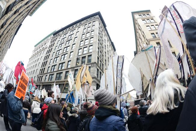 紀念三角衣廠大火106周年,大紐約地區車衣工人代表等24日在曼哈頓華盛頓街與格林街交口的原衣廠大樓舉行紀念會,與會者舉著的一件件女士襯衫上註明喪生的女工的名字及年齡。(記者許振輝/攝影)