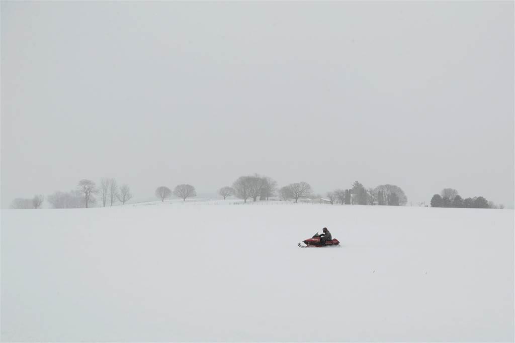 暴風雪中,賓州一名男子在白茫茫的曠野中駕著雪車急速前進。 (美聯社)