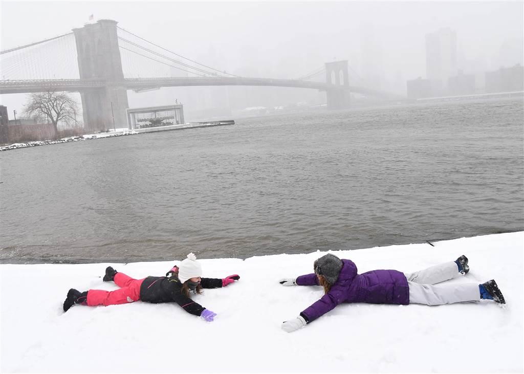 小女孩在雪地上玩著snow angel,遠處為紐約市東河上的布碌崙橋。(Getty Images)