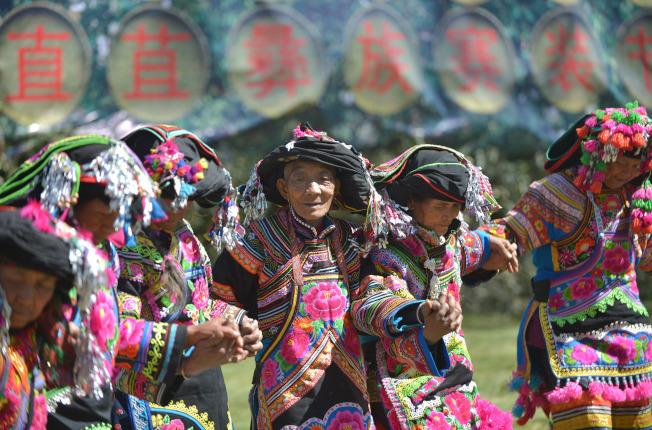 彝族賽裝節已有1351年歷史,村民們在當天都會身著自己親手縫製的彝族服飾,賽裝比美、跳腳狂歡。 (新華社)