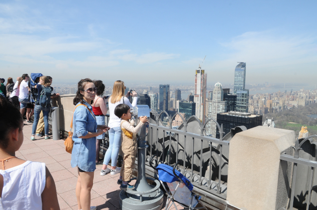 遊客在洛克斐勒中心觀景台觀賞中央公園及建築群。右二為新建中的Central Park Tower (右二),完工後樓高1550呎,是全世界最高的公寓住宅;右一大樓為One 57。(記者許振輝/攝影)