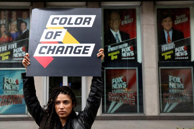 歐萊利被開除後,示威者舉牌到新聞集團總部大樓前示威。(路透)