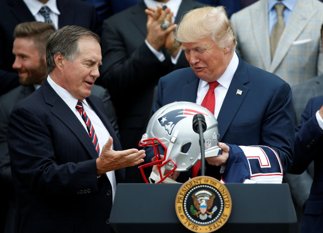 川普總統(右)接受愛國者隊教練致贈的球隊頭盔。(路透)